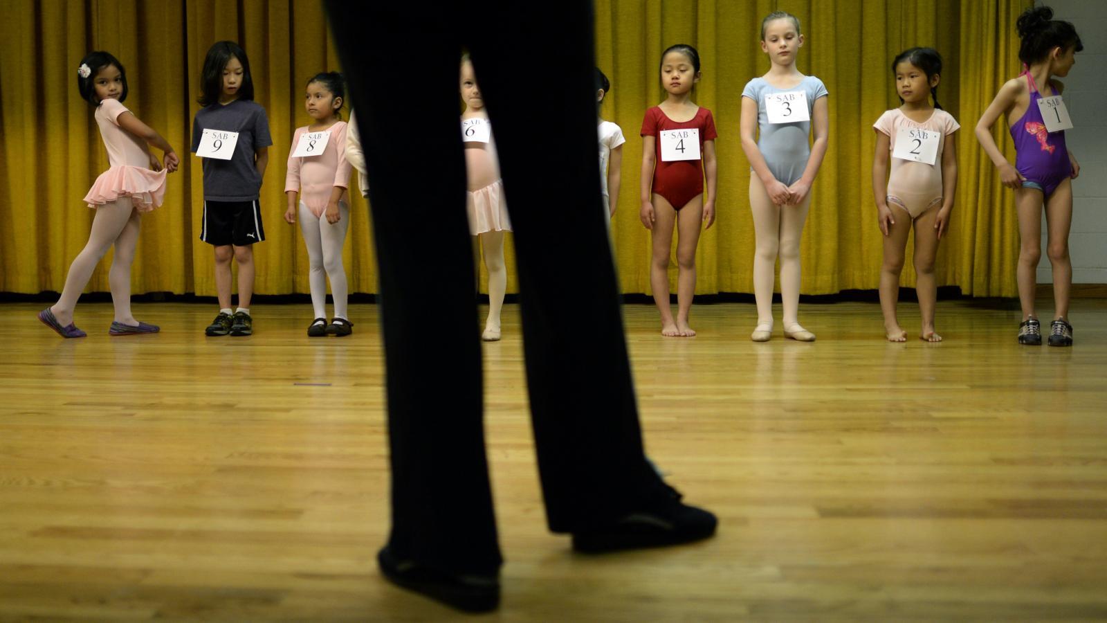 A teacher stands before a class of child ballerinas during an audition.